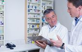 Pharmacists holding medication and writing a prescription in the pharmacy