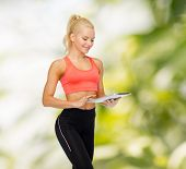 sport, exercise, technology, internet and healthcare concept - smiling sporty woman with tablet pc computer