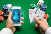 casino, online gambling, technology and people concept - close up of poker player with playing cards, smartphone and chips at green casino table