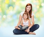 childhood, motherhood, parenting and relationship concept - happy mother with adorable little girl over green lights background