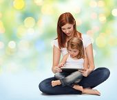 childhood, parenting and technology concept - happy mother with adorable little girl and tablet pc computer over green lights background
