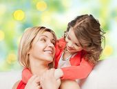 people, happiness, love, family and motherhood concept - happy mother and daughter hugging and talking over green lights background