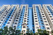 stock photo of highrises  - A typical Singapore highrise public housing estate against a blue sky - JPG