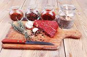 pic of flesh  - fresh raw beef meat fillet flesh with peppercorn and thyme ready to grill on wood figured old style board  over table with spices in glass - JPG