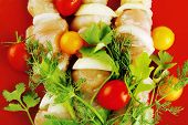 raw chicken kebabs on red served with tomatoes