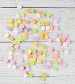 A group of Valentine's candy hearts scattered in a random pattern on a rustic whitewashed wood table. Overhead shot in square format.