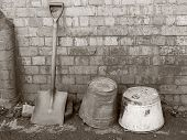 picture of spade  - Black and white toned sepia retro photograph of old vintage buckets and a spade resting against an old Victorian wall - JPG