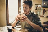 image of lunch  - Young man having a lunch break with a tasty ham sandwich and a glass of coke - JPG