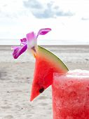 foto of watermelon  - Close up piece of watermelon on the top of watermelon juice glass against beach background - JPG