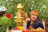foto of curvaceous  - Beautiful Russian girl with a curvaceous rosy and happy sitting at a table with a samovar drying bagels budlikami strawberries in the spring blooming garden bright colors and spring - JPG