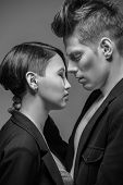 foto of tuxedo  - Young fashionable couple in tuxedos posing in the studio - JPG