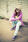picture of snickers  - Beautiful teenage girl in cap and sunglasses sits on a skateboard near brick wall vertical photo with warm retro tonal correction effect instagram old style filter - JPG