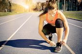image of sportive  - Young sportive woman getting ready to start running workout  - JPG