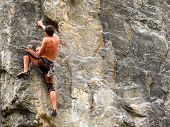 stock photo of climbing wall  - Young white man climbing a steep wall in mountain - JPG