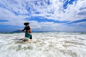stock photo of sanitation  - Unknown Sanitation Worker Cleaning Doc Let Beach Vietnam - JPG