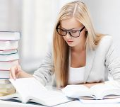 foto of piles  - student with pile of books and notes studying indoors - JPG