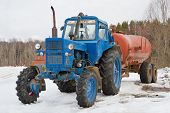 stock photo of tractor-trailer  - Old farm tractor with trailer in winter - JPG