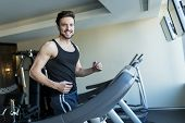 image of treadmill  - Young man training on a treadmill in the gym - JPG