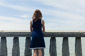 stock photo of balustrade  - A young woman wearing a blue dress is standing by a wall with concrete balustrades on a promenade and is admiring the seaside on a sunny day - JPG
