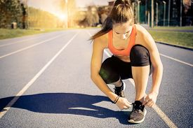 image of athletic woman  - Young sportive woman getting ready to start running workout  - JPG