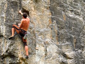 picture of rocking  - Young white man climbing a steep wall in mountain - JPG