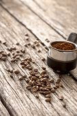 Постер, плакат: Scattered Coffee Beans And Freshly Ground Coffee Beans In The Metal Measure Of A Coffee Machine