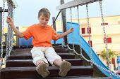 Caucasian Boy In Orange Shirt Sitting On Suspension Bridge On Playground, Hands On Chains
