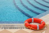 Red Lifebuoy With Yellow Ropes On Tiled Floor Near Swimming Pool With Stairs
