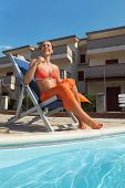 Young Woman In Orange Bikini And Pareo Sitting On Beach Chair Near Pool And Smiling poster