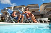 Young Mother In Orange Pareo And Son Sitting On Beach Chair Near Pool And Smiling