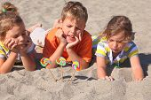 Little Boy And Two Girls Lying On Beach, Chin On Hands, Lollipops Stick In Sand