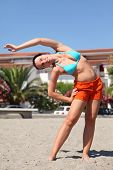 Young Beauty Woman Making Gym Exercises On Beach And Smiling, House And Palms
