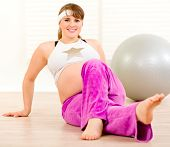 Smiling beautiful pregnant woman making gymnastics at living room