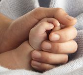 stock photo of holding hands  - man holding a baby hand extreme close - JPG