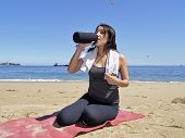Woman Resting And Drinking After Exercise