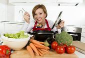 ������, ������: Young Happy And Attractive Home Cook Woman In Red Apron At Domestic Kitchen Holding Saucepan Tasting