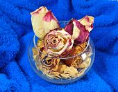 Dried up flowers of roses and leaves in a glass glass