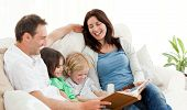 pic of keepsake  - Happy parents looking at a photo album with their children on the sofa - JPG