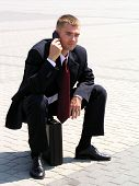 Businessman Using A Mobile Phone Sitting On A Briefcase