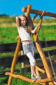 Cute Little Girl With Blond Long Hair Playing On Wooden Chain Sw