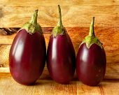 image of cutting board  - three fresh eggplants on wood cutting board - JPG