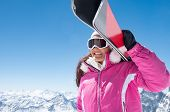 Sporty woman carrying ski on shoulder and looking snowy mountain. Smiling girl carrying a pair of re poster
