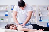 Young doctor chiropractor massaging female patient woman poster