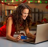 Woman With Credit Card Typing On Laptop In Christmas Kitchen poster