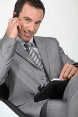 Ejecutivo seguro masculino con teléfono móvil y diario