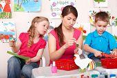 Child with teacher in play room. Preschooler.