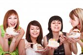 Group of happy young woman eating cake. Isolated.