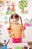 Little girl preschooler painting in classroom.