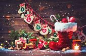 Christmas background. Advent calendar and Santas shoe with gifts on rustic wooden background poster