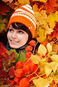 Girl in autumn orange hat on leaf group with flower. Outdoor.